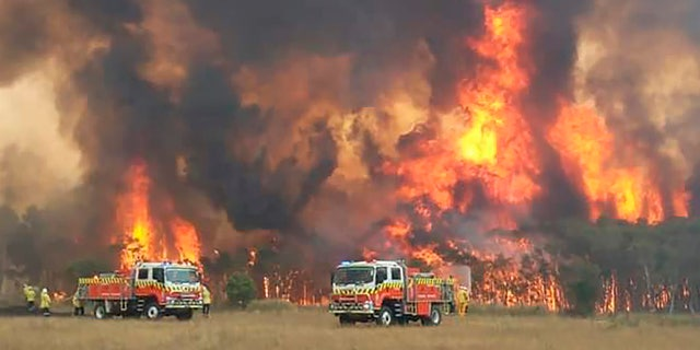 In this image dated Dec. 30, 2019, and provided by NSW Rural Fire Service via their twitter account, firefighters are seen as they try to protect homes around Charmhaven, New South Wales.