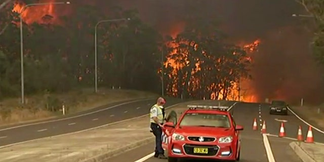 In this image made from video, officials block the Princes Highway as wildfires approach in South Coast, New South Wales Australia, Tuesday, Dec. 31, 2019.