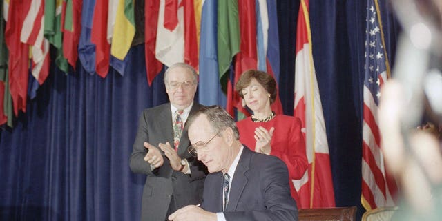 President George H. W. Bush, center, signs the North American Free Trade Agreement during a ceremony at the Organization of American States headquarters, Thursday, Dec. 17, 1992, Washington, D.C. Canadian Ambassador Derek Burney and U.S. Trade Representative Carla Hills applaud during the signing. The president predicted an explosion of growth throughout North America as he signed the agreement. (AP Photo/Dennis Cook)
