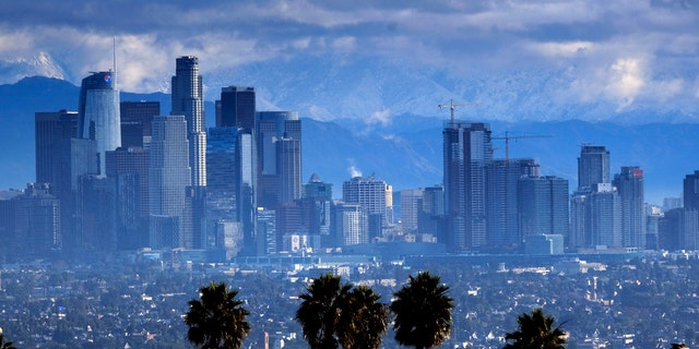 Heavy storm clouds and a dusting of snow are seen in the San Gabriel mountain range behind downtown Los Angeles.
