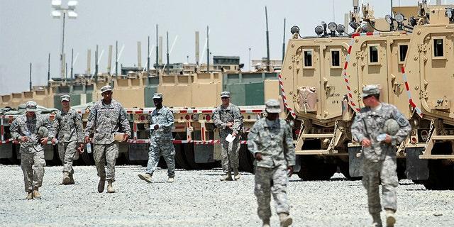 U.S. soldiers walk near vehicles at Camp Arifjan, Kuwait as they prepare to head to Iraq.