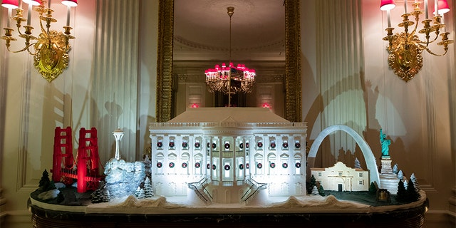 A White House made of gingerbread surrounded by landmarks from around the country in the State Dining Room during the 2019 Christmas preview. [AP Photo/Alex Brandon)