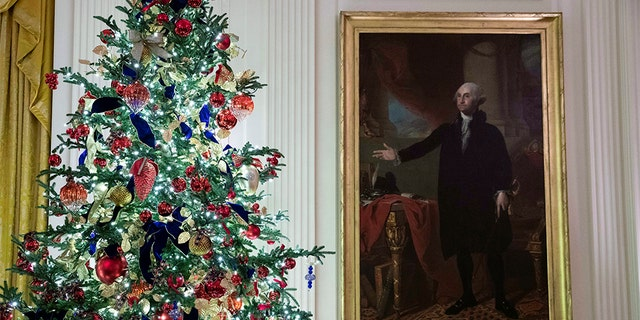 A decorated tree stands next to the portrait of President George Washington in the East Room during the 2019 Christmas preview at the White House, Monday, Dec. 2, 2019, in Washington. [AP Photo/Alex Brandon)