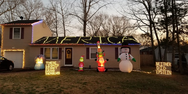 """N.J. resident Kevin Gibson Jr placed two signs on his yard, one that says, """"These lights didn't hang themselves,"""" and another that reads, """"Neither did Epstein."""""""