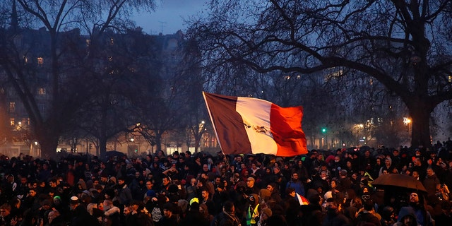 A person waves a French tricolor at the end of a demonstration Tuesday, Dec.17, 2019, in Paris. People from across the French workforce walked off the job Tuesday to resist a higher retirement age and to preserve a welfare system they fear their business-friendly president wants to dismantle. (AP Photo/Francois Mori)