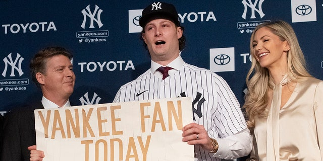 New York Yankees pitcher Gerrit Cole, center, holds a sign he used as a young Yankees fan, as he is introduced as the baseball clubs newest player during a baseball media availability, Wednesday, Dec. 18, 2019 in New York. He is joined by team owner Hal Steinbrenner, left, and his wife, Amy Cole.(AP Photo/Mark Lennihan)