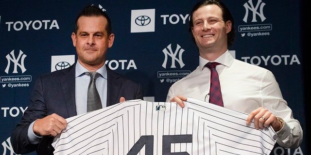 New York Yankees manager Aaron Boone, left, and pitcher Gerrit Cole hold up a jersey as Cole is introduced as the baseball club's newest player during a media availability, Wednesday, Dec. 18, 2019 in New York. The pitcher agreed to a 9-year, $324 million contract. (AP Photo/Mark Lennihan)