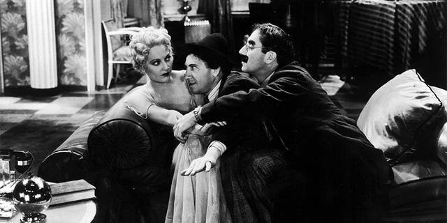 """American comedian Groucho Marx (1890 - 1977, right) and his brother Chico (1887 - 1961) pay homage to the college widow, played by Thelma Todd (1906 - 1935), in a scene from """"Horse Feathers,"""" directed by Norman Z. McLeod, 1932."""