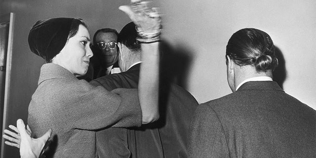 """Actress Anna Kashfi, formerly married to actor Marlon Brando, delivers a hard slap in the face to her ex-husband as the two left the courtroom after Brando won a long fight to increase his visitation rights to his three-year-old son by Miss Kashfi. Brando's hair is still styled for his role in """"Mutiny on the Bounty."""""""