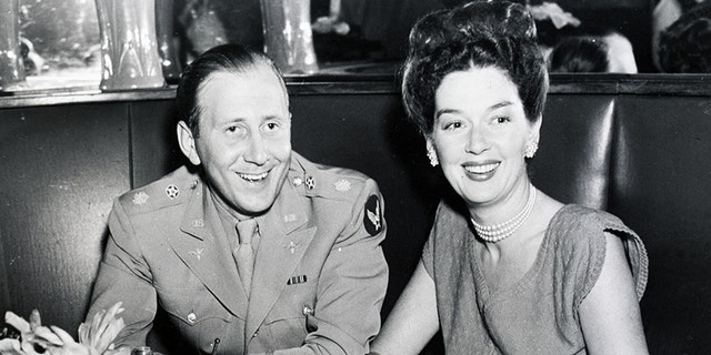 """Major Fred Brisson, just back from Europe where he served as General's Arnold's Chief of radio activities, and his lovely wife, screen star Rosalind Russell, are shown enjoying their happy reunion at the famous Stork Club, in New York. Miss Russell recently completed her new picture """"She Wouldn't Say Yes"""" and came east to be with her husband. This photo was taken in 1945."""