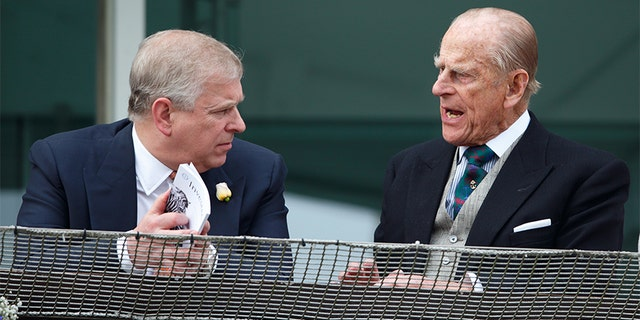 Prince Philip, Duke of Edinburgh and Prince Andrew, Duke of York watch the racing from the balcony of the Royal Box as they attend Derby Day during the Investec Derby Festival at Epsom Racecourse on June 4, 2016 in Epsom, England.