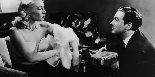 Edward D. Wood Jr. (1924 - 1978) watches actress Dolores Fuller remove her white angora sweater in a still from the film