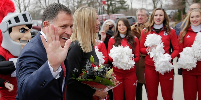 New Rutgers NCAA college football manager Greg Schiano greets supporters as he arrives for a news discussion in Piscataway, N.J., with his wife, Christy, Wednesday, Dec. 4, 2019. After an on-again, off-again courtship, Schiano is behind as Rutgers football coach. (AP Photo/Seth Wenig)