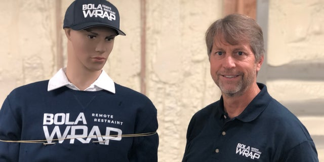 David Norris, Wrap Technologies CEO, demonstrates the BolaWrap on a mannequin.