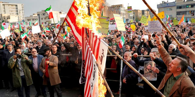 Demonstrators burn representations of the U.S. flag during a pro-government rally denouncing last week's violent protests over a fuel price hike, in Tehran, Iran, Monday, Nov. 25, 2019. (AP Photo/Ebrahim Noroozi)