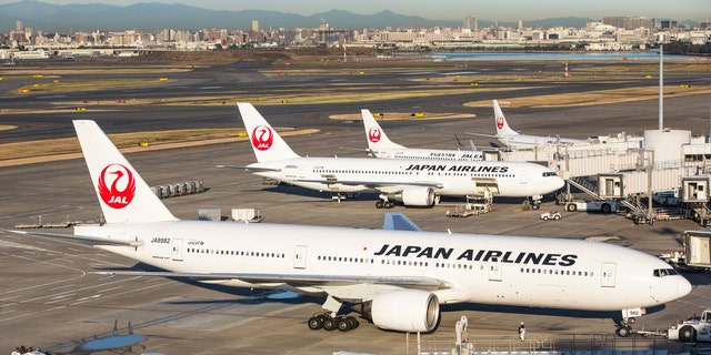 Tokyo, Japan - December 4, 2012: Japan Airlines airplane and JAL Express airplane at Tokyo International Airport (Haneda Airport) in Japan. Some workers are working at the airport area. It is located in Ota Ward, Tokyo, Japan. Tokyo International Airport is the busiest airport in Japan.