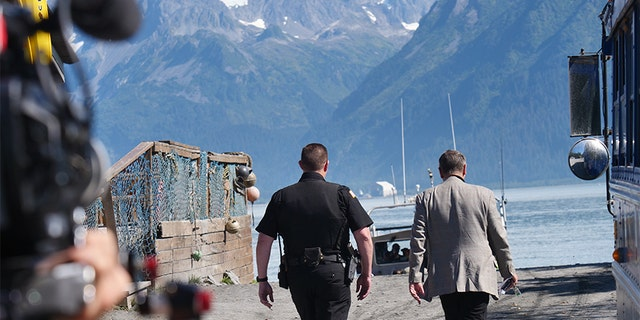 Frank Parlato and Lt. Nickell walking down towards the harbor. Production crew included.