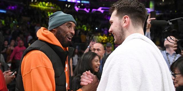 Former Los Angeles Laker Kobe Bryant, left, greets Dallas Mavericks guard Luka Doncic after an NBA basketball game Sunday, Dec. 29, 2019, in Los Angeles. The Lakers won 108-95. (AP Photo/Michael Owen Baker)