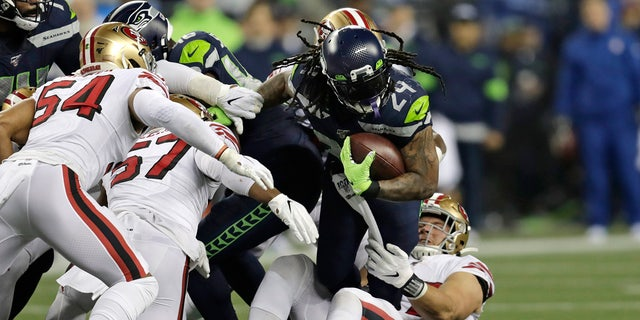 Seattle Seahawks' Marshawn Lynch (24) carries on a fourth-and-one but is pulled down short during the first half of an NFL football game against the San Francisco 49ers, Sunday, Dec. 29, 2019, in Seattle. (AP Photo/Stephen Brashear)