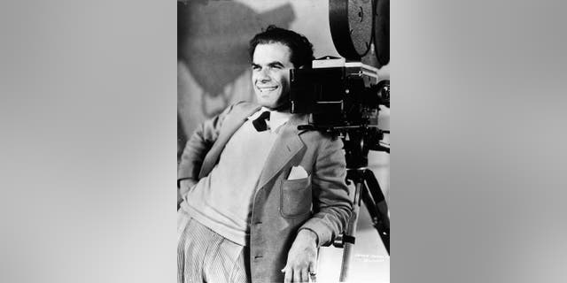 The Italian American director and screenwriter Frank Capra smiling while leaning on a camera, circa 1930s.