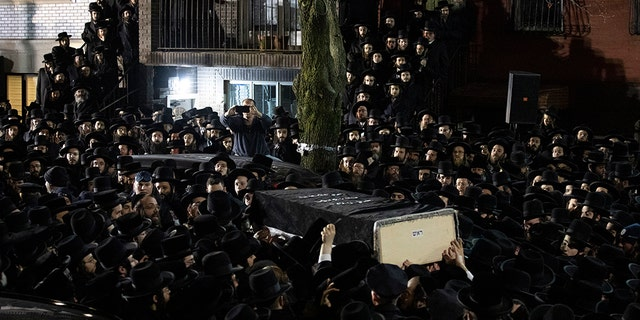 Orthodox Jewish men carry Moshe Deutsch's casket outside a Brooklyn synagogue following his funeral on Wednesday in New York. Deutsch was one of the victims killed in Tuesday's shooting in Jersey City, N.J.