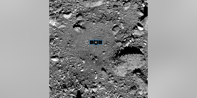This image released by NASA shows sample site Nightingale, OSIRIS-REx's primary sample collection site on asteroid Bennu. The image is overlaid with a graphic of the OSIRIS-REx spacecraft to illustrate the scale of the site.