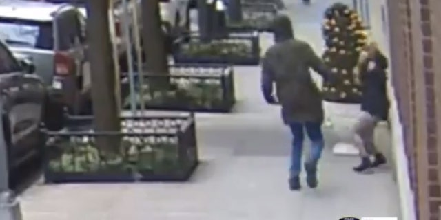 The suspect can be seen swinging at a 21-year-old woman who was on her phone.
