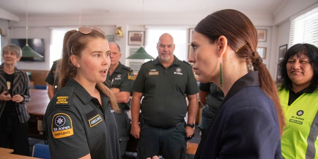 New Zealand's Prime Minister Jacinda Ardern, right, talks with first responders in Whakatane, New Zealand, Tuesday, Dec. 10, 2019.