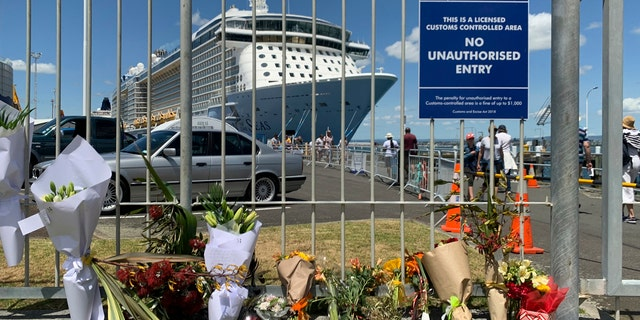 Flowers are laid on makeshift memorial is seen in front of cruise ship Ovation of the Seas, in Tauranga, New Zealand, Tuesday, Dec. 10, 2019.