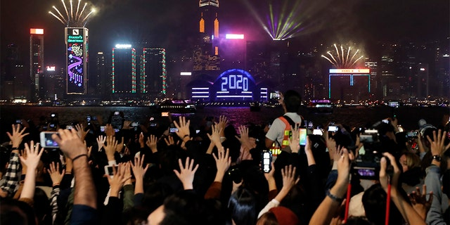 Protesters hold up their hands to symbolize the five demands of the pro-democracy movement as New Year's fireworks light up the sky during a demonstration in Hong Kong, Wednesday, Jan. 1, 2020. (Associated Press)