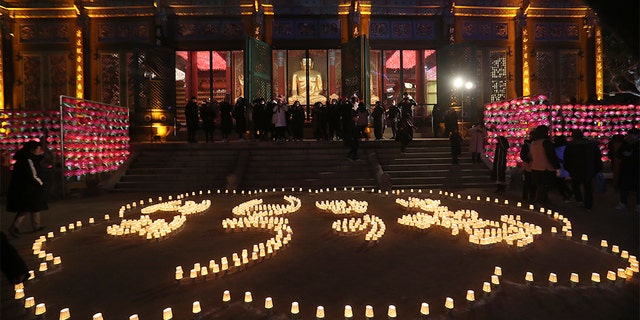 """Buddhists light candles to form letters meaning, """"Best wishes for a Happy New Year,"""" during New Year celebrations at Jogyesa Buddhist temple in Seoul, South Korea, Wednesday, Jan. 1, 2020. (Associated Press)"""