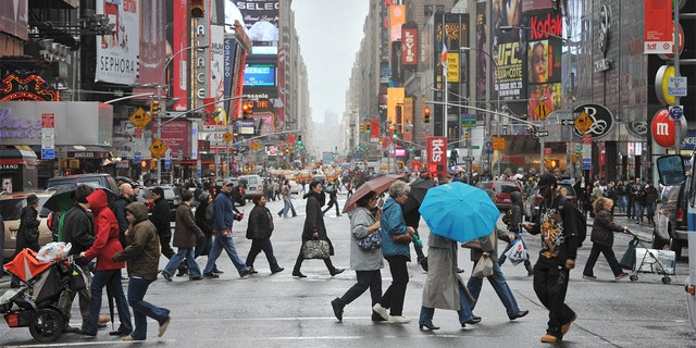 Crowds of New Yorkers and visitors cross the street in Times Square. (FILE)