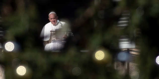 Pope Francis, framed by the St. Peter's Square Christmas tree, reads his message during the Angelus noon prayer he recited from the window of his studio, at the Vatican, Sunday, Dec. 1, 2019. (AP Photo/Alessandra Tarantino)