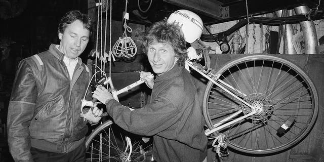 "FILE - In this May 16, 1985, file photo, actor John Ritter, left, checks out the bicycle of fellow actor Rene Auberjonois, center, backstage at the Eugene O'Neill Theatre in New York following a performance of the Broadway musical, ""Big River: The Adventures of Huckleberry Finn."""