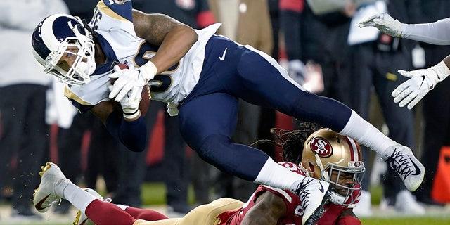 Los Angeles Rams running back Todd Gurley II (30) is tackled by San Francisco 49ers cornerback Richard Sherman, bottom, during the second half of an NFL football game in Santa Clara, Calif., Saturday, Dec. 21, 2019. (AP Photo/Tony Avelar)