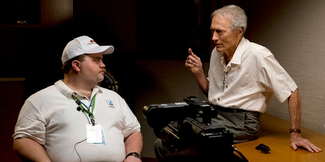 "In this image released by Warner Bros. Pictures, director Clint Eastwood speaks with actor Paul Walter Hauser as they work during the filming of the movie ""Richard Jewell."""