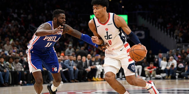 Washington Wizards forward Rui Hachimura (8), of Japan, dribbles the ball as he is defended by Philadelphia 76ers forward James Ennis III (11) during the second half of an NBA basketball game, Thursday, Dec. 5, 2019, in Washington. The Wizards won 119-113. (AP Photo/Nick Wass)