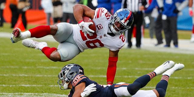 New York Giants running back Saquon Barkley (26) flips over Chicago Bears cornerback Kyle Fuller (23) during the second half of an NFL football game in Chicago, Sunday, Nov. 24, 2019. (AP Photo/Charles Rex Arbogast)