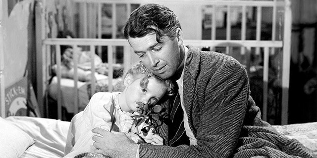 "American actors James Stewart (1908 - 1997), as George Bailey, and Karolyn Grimes as his daughter Zuzu, in a scene from ""It's a Wonderful Life."" The film was directed by Frank Capra in 1946."