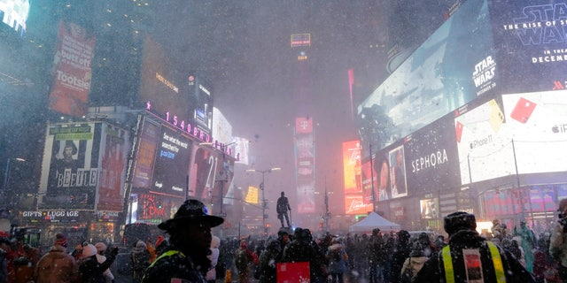 Pedestrians observe a snow squall in Times Square Wednesday, Dec. 18, 2019, in New York.