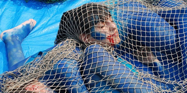 The dead-serious protesters laid on a blue tarp on the ground, with their tangled limbs painted blue, and blood-like red paint dripping from their mouths.