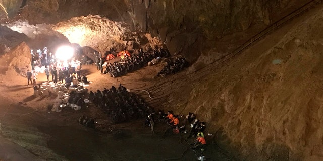 In this June 26, 2018, file photo, emergency rescue teams gather in the staging area during the cave rescue in Mae Sai, Chiang Rai province, northern Thailand.
