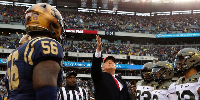 President Donald Trump throws the coin before the start of the Army-Navy college football game in Philadelphia, Saturday, Dec. 14, 2019. (AP Photo/Jacquelyn Martin)
