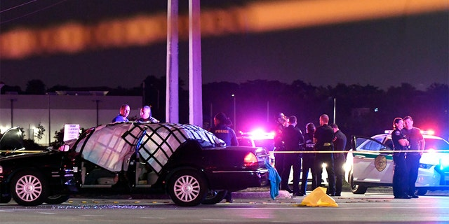 EDS NOTE: GRAPHIC CONTENT - In this Thursday, Dec. 5, 2019, photo authorities investigate the scene of a shooting in Miramar, Fla. The FBI says several people, including a UPS driver, were killed after robbers stole the driver's truck and led police on a chase that ended in gunfire at a busy South Florida intersection during rush hour. (Taimy Alvarez/South Florida Sun-Sentinel via AP)