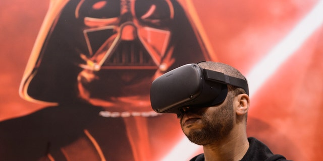 An attendee plays the 'Vader Immortal: A Star Wars VR Series
