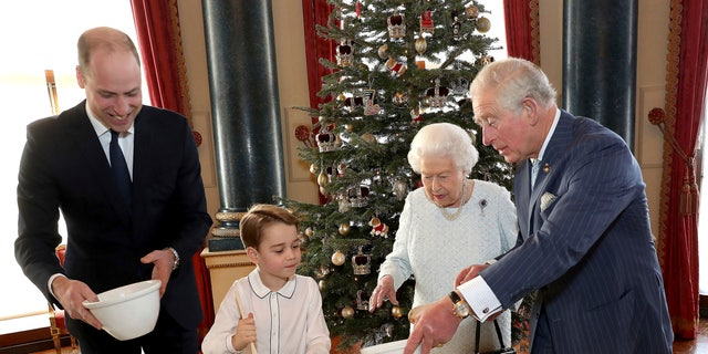 In this photo provided by Buckingham Palace, Britain's Queen Elizabeth, Prince Charles, Prince William and Prince George smile as they prepare special Christmas puddings in the Music Room at Buckingham Palace, London, as part of the launch of The Royal British Legion's Together at Christmas initiative.