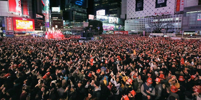 People gather to welcome the arrival of the New Year at a crossing in Shibuya district in Tokyo Wednesday, Jan. 1, 2020. (Associated Press)