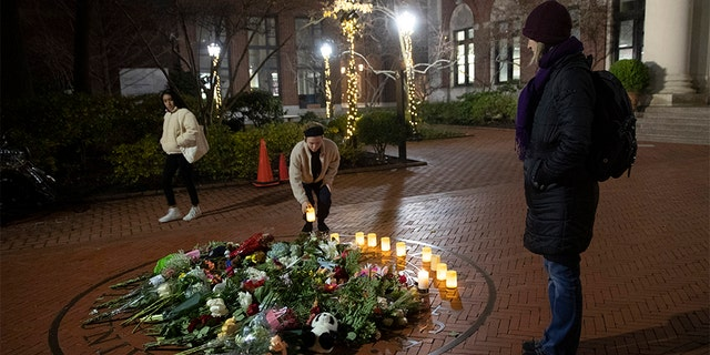 People pause and place a candle at a makeshift memorial for Tessa Majors inside the Barnard campus on Thursday.