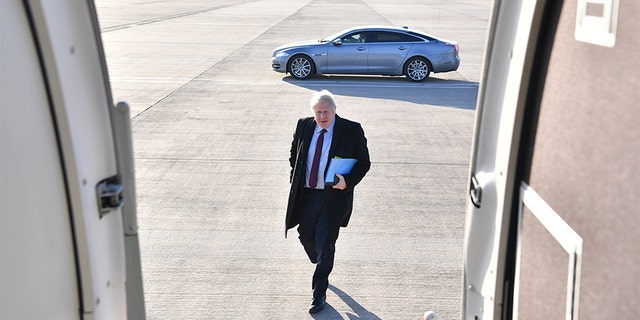 Britain's Prime Minister and Conservative Party leader Boris Johnson boards a plane at Doncaster Sheffield Airport in Doncaster, England, on Monday, during campaigning ahead of the general election on Dec. 12.