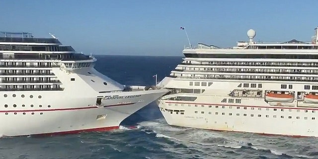 "The Carnival Glory cruise ship, right, crashes into the Carnival Legend on Friday morning. The cruise line currently believes the collision was caused by ""spontaneous wind gusts and strong currents."""